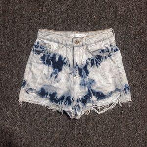 Distressed tie dye denim shorts